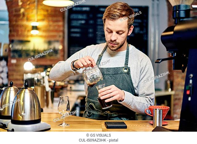Male barista pouring coffee at coffee shop kitchen counter