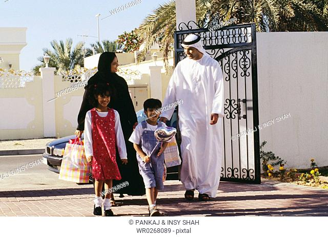 A family returns home after an outing and shopping