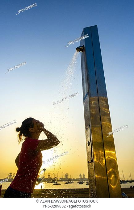 Las Palmas, Gran Canaria, Canary Islands, Spain. A female jogger at sunrise cooling down under a beach shower following morning run on the city beach in Las...