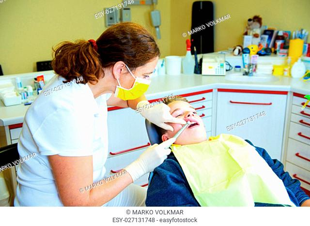 teenager is treated by female dentist in dental surgery