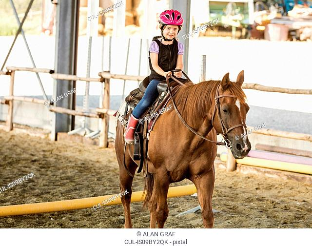 Girl horse riding in equestrian arena, portrait