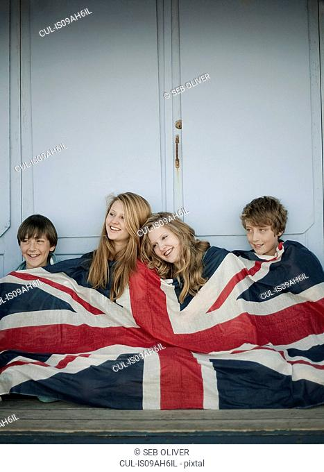 Portrait of sisters and brothers sitting on porch wrapped in union jack flag
