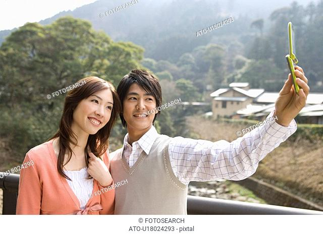 Man taking a picture of themselves with a mobile phone, side view, Japan