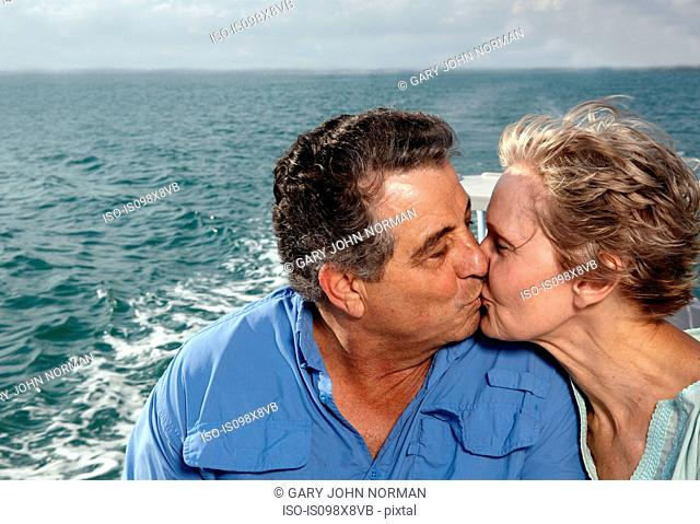Senior couple kissing on motorboat