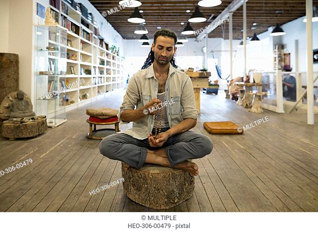 Man sitting in lotus position with prayer beads in new age shop