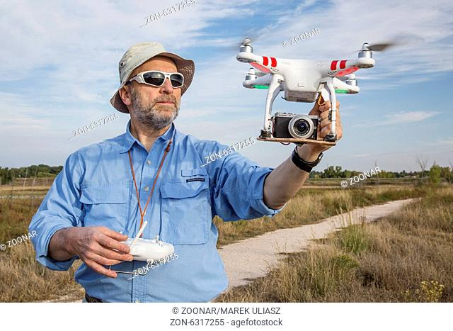 FORT COLLINS, CO, SEPTEMBER 28, 2014: A senior male pilot and photographer is launching the DJI Phantom 2 quadcopter drone with Panosonic Lumix GM1 camera on...