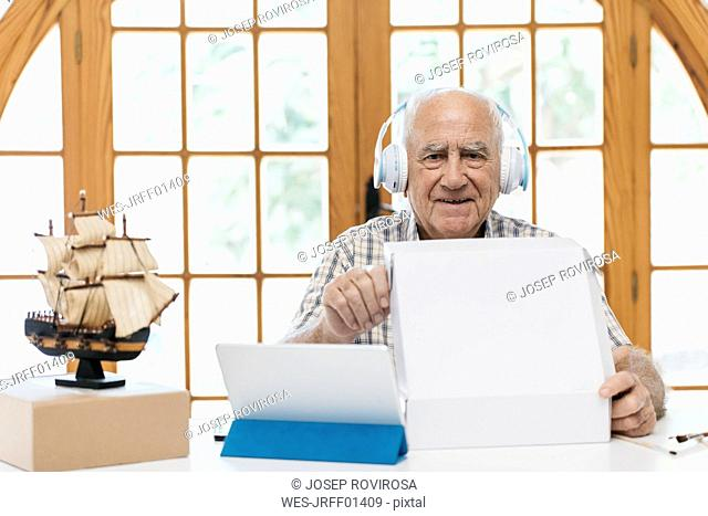 Portrait of confident senior man wearing headphones with tablet, model ship and package on table