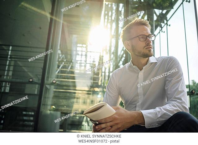Businessman holding book looking away
