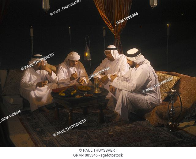 Ramadan: men sitting in Arabian tent for Iftar (fast-breaking meal after sunset)