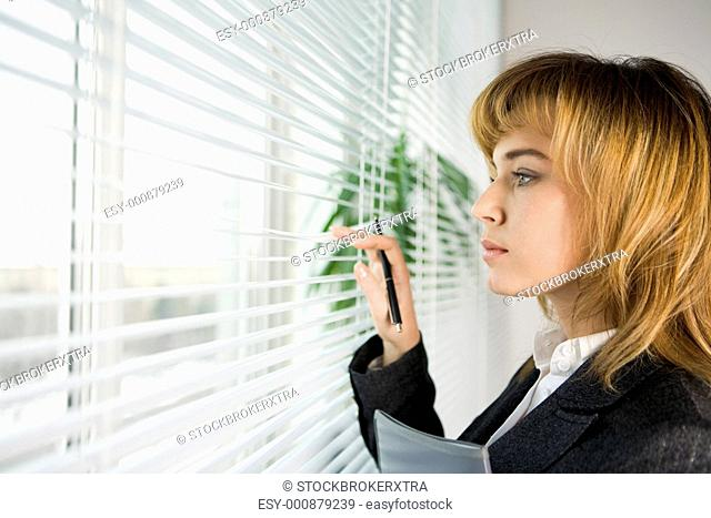 Profile of confident female looking outside through venetian blinds