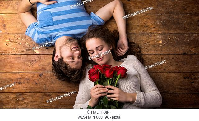 Young couple in love lying on wooden floor