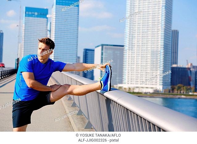 Young Caucasian man stretching in metropolitan area