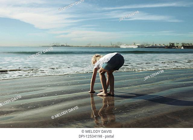 A young girl plays in the wet sand along the shoreline; Long Beach, California, United States of America
