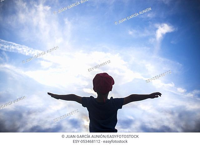 4 years old boy pretending to fly over cloudy sky. Encourage children Imagination concept