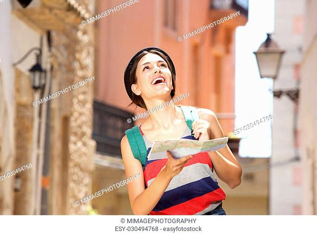 Portrait of a cheerful young woman walking in town with bag and map