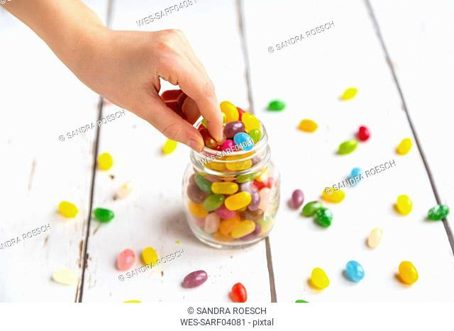 Glass of colourful sweet jellybeans on white wood, hand taking one