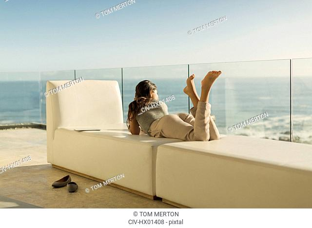 Woman on luxury balcony relaxing laying on bench looking at sunny ocean view