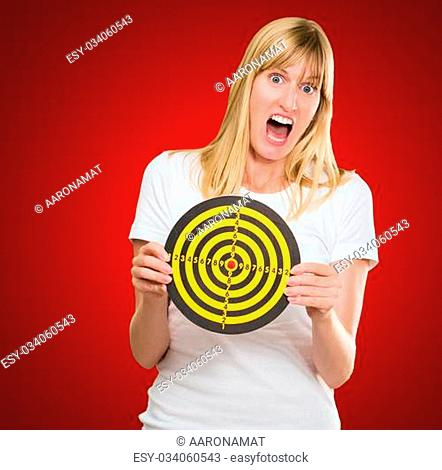 Afraid Woman Holding Dartboard against a red background