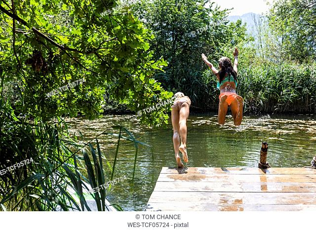 Two carefree girls jumping into pond