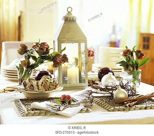 Christmas table with stollen, lantern and Christmas roses