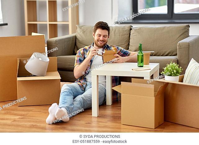 smiling man eating takeaway food at new home