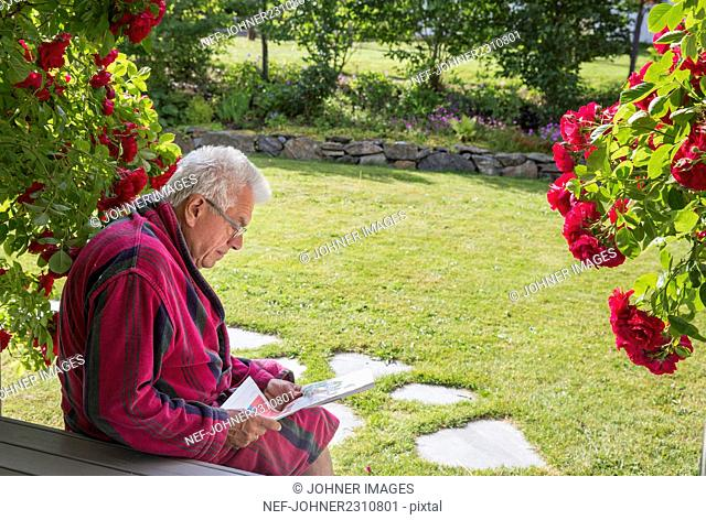 Senior man reading newspaper in garden