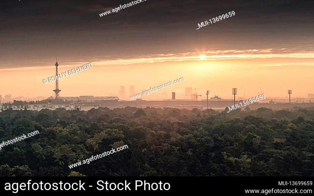 Sunrise in autumn over the misty Grunewald with a view of the radio tower and the television tower in Berlin