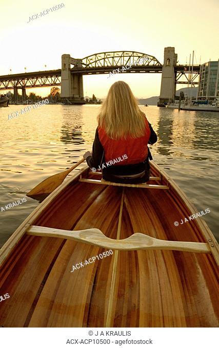 Girl canoeing on False Creek towards Burrard Bridge, Vancouver, British Columbia, Canada