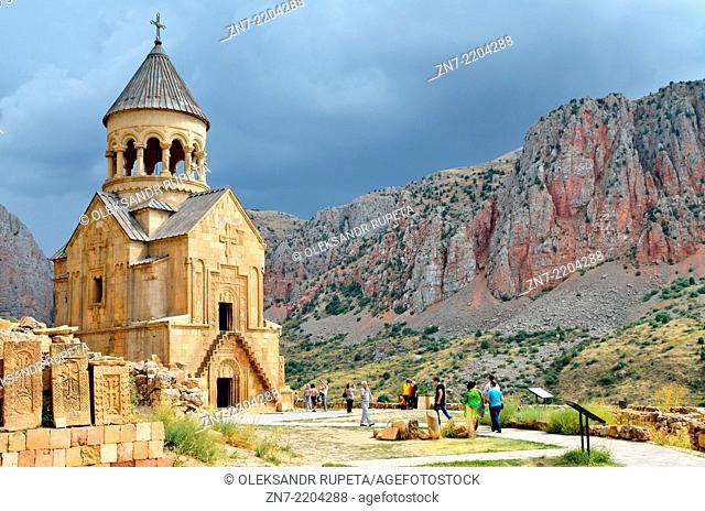 Khachkars and Surp Astvatsatsin (Holy Mother of God) church with red cliffs in background, Noravank Monastery, Armenia