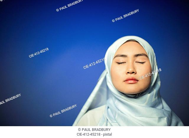 Serene young woman wearing blue silk hijab