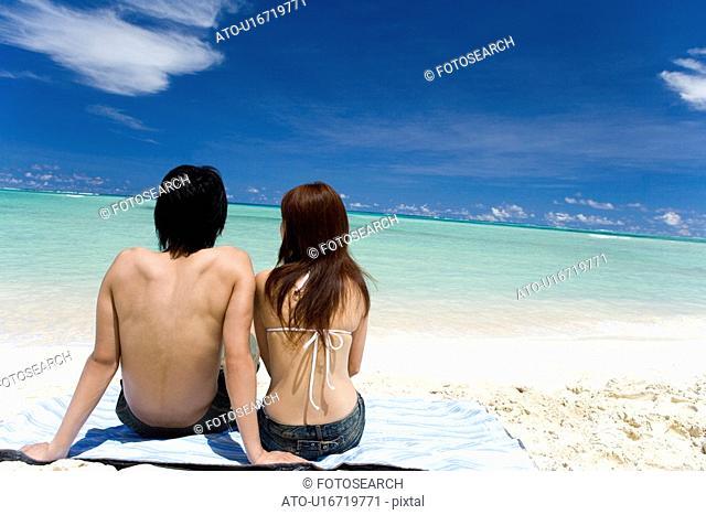 Young couple sitting on beach, Saipan, USA
