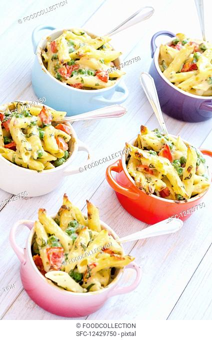 Mini servings of pasta bake with peas, cherry tomatoes in a creamy white sauce served in small colourful pots with forks