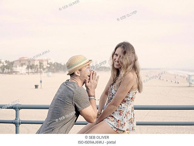 Young couple fooling around on Santa Monica pier, California, USA