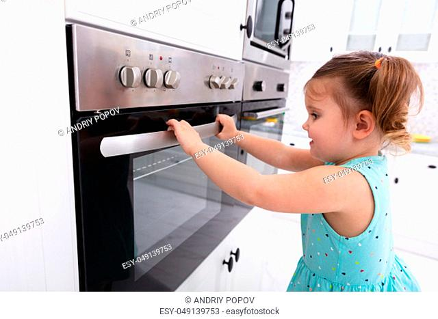 Little Girl Playing With Electric Microwave Oven In The Kitchen