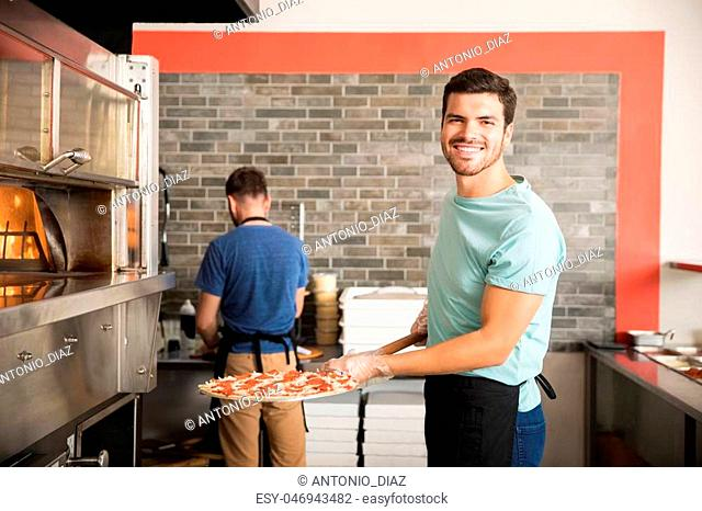 Smiling chef in black apron putting pizza into the oven with peel at restaurant kitchen
