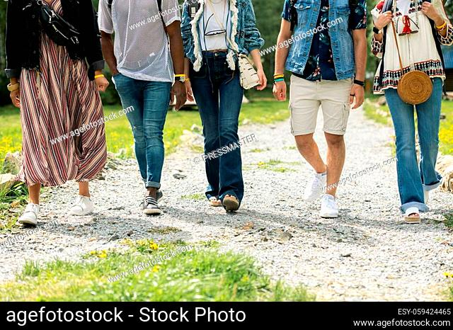 Group of unrecognizable friends in hippie outfits walking on path together outdoors