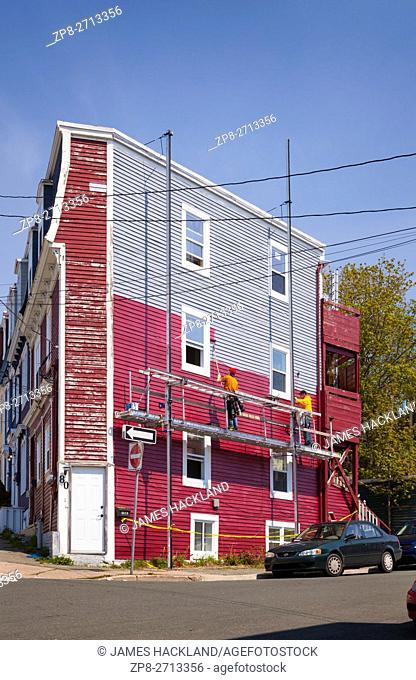 Painters paiting a corner row house (Jellybean Row) in downtown St. John's, Avalon Peninsula, Newfoundland, Canada