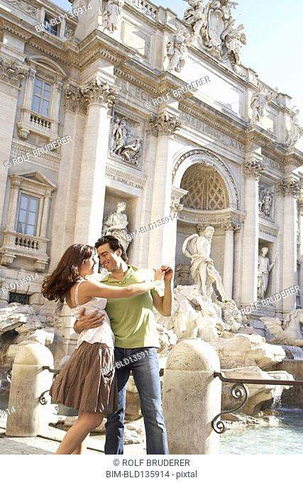 Caucasian couple dancing outside Fontana di Trevi, Rome, Italy