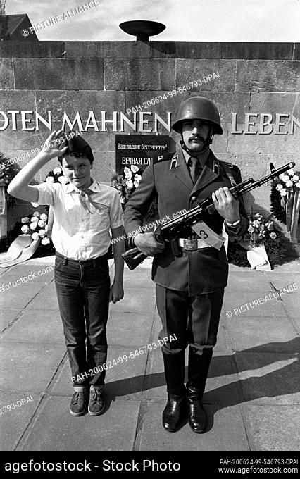 "08 May 1985, Saxony, Eilenburg: Soviet soldier with Kalashnikov and Thälmann pioneer with pioneer salute. """"The dead exhort the living"""""