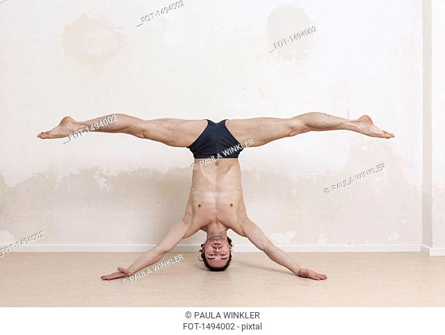 Portrait of upside down man with legs apart performing headstand yoga exercise