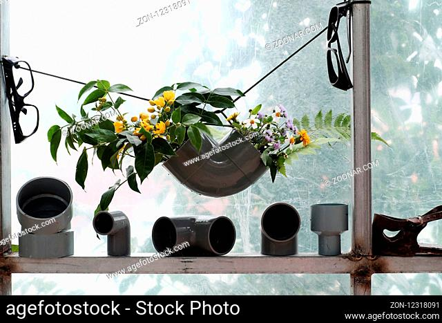 Leisure activities with recycle from waste to make flower vase to decoration home, colorful daisy in water pipe on white background