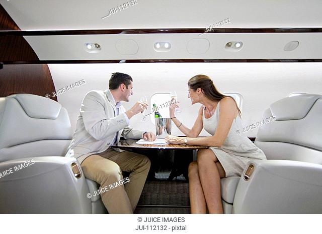 Smiling couple drinking champagne and looking out of window in private jet