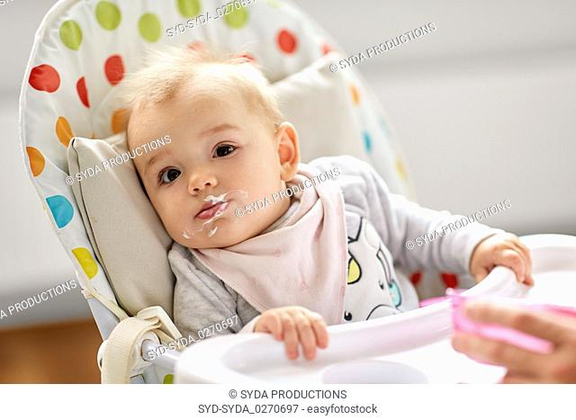 little baby girl eating in highchair at home