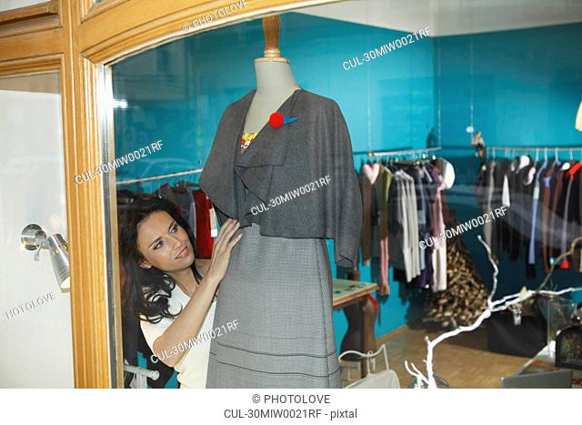 woman in shop window dressing mannequin