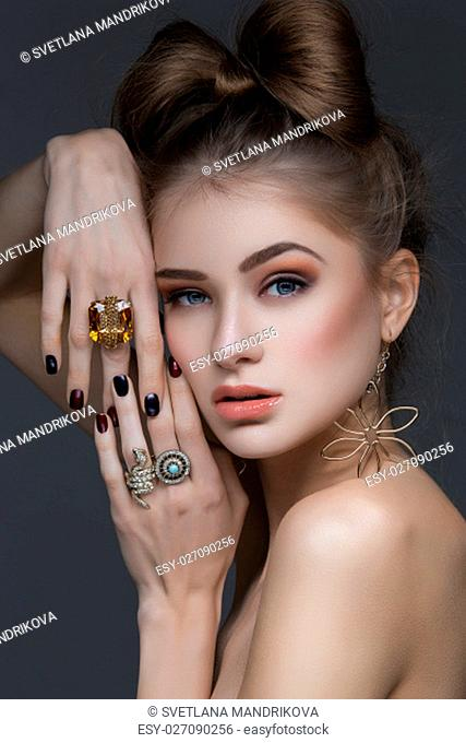 Beautiful young woman with hair bow and rings. Beauty shot. Copy space
