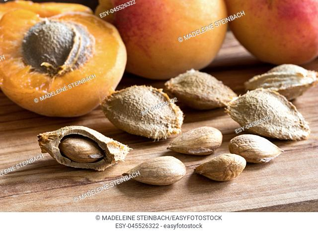 Apricot kernels and ripe apricots on a wooden background