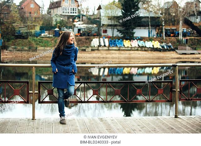 Smiling Caucasian woman leaning on bridge railing near river