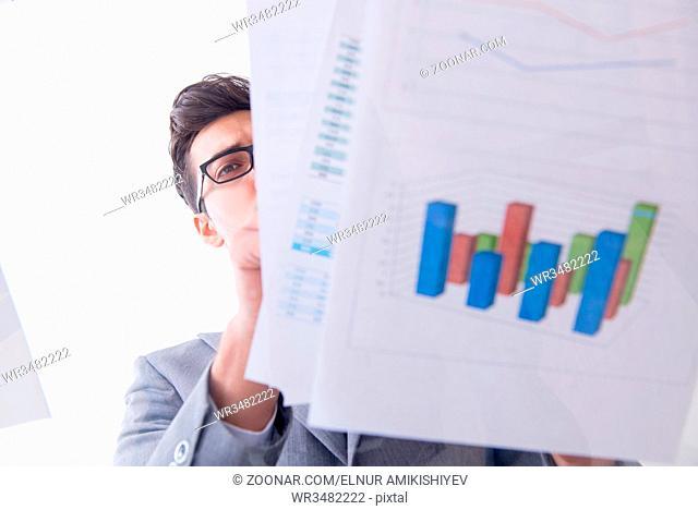 Businessman looking at financial charts and graphs
