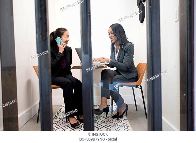 Two businesswomen in office, using laptop, talking on smartphone