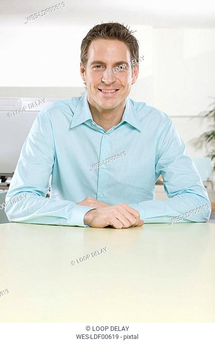Germany, Munich, young man in office, arms crossed, smiling, portrait, close-up